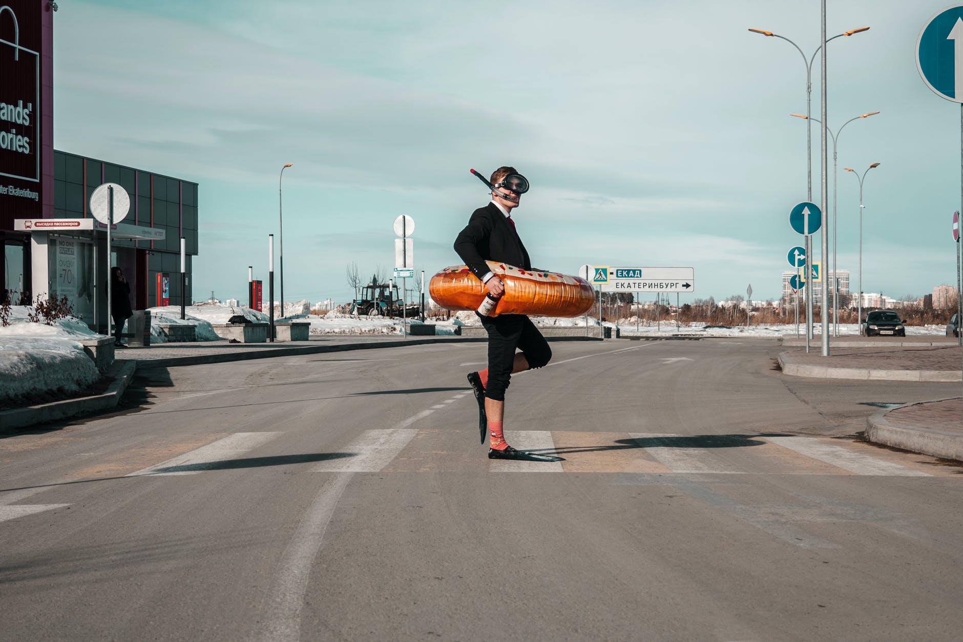 strange man with swimming equipment on street